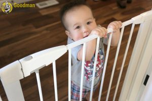 A toddler holding onto a stair gate